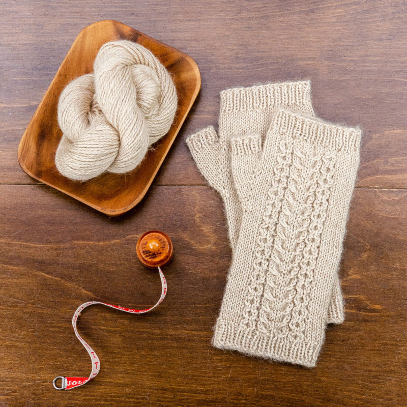 A pair of fingerless mitts is photographed on a table from above next to yarn and a tape measure | Free Knitting Pattern - Cable Wristwarmers