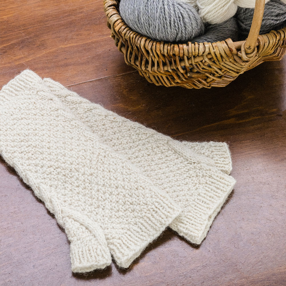 Textural fingerless mitts with a cable panel up the inner-wrist which wraps around the thumb.