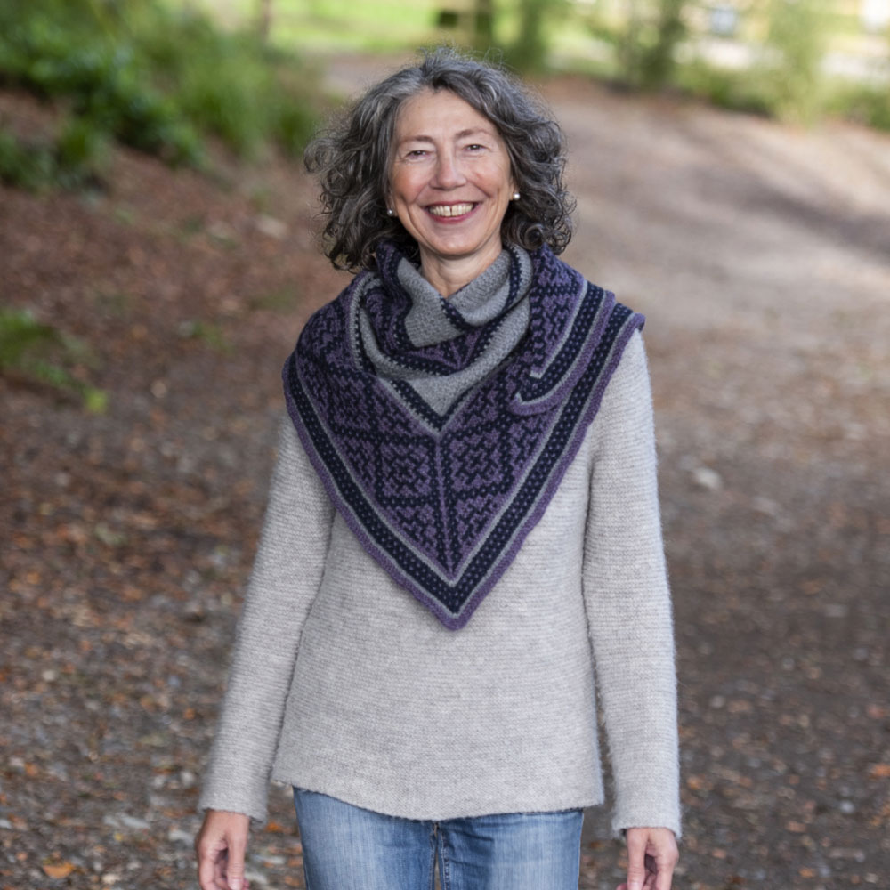 Mosaic knit shawl in shades of purple, grey and navy. The colourwork looks like ornate tiling.