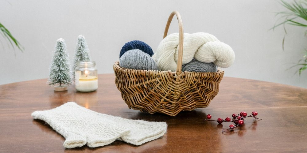 A basket of yarn is on a table, along with a pair of fingerless mitts, some red berries, a candle and some decorative christmas trees.