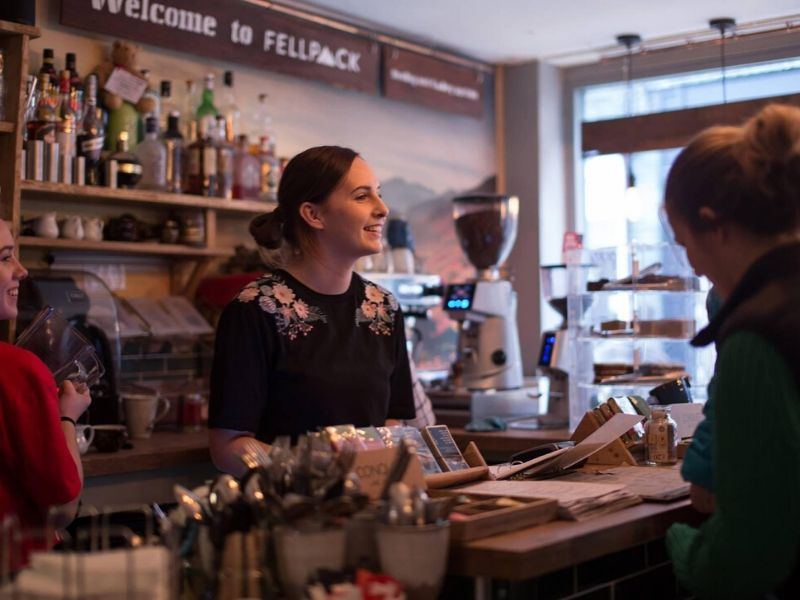A woman is serving a customer at the Fellpack café. She is smiling and the atmosphere looks very inviting!