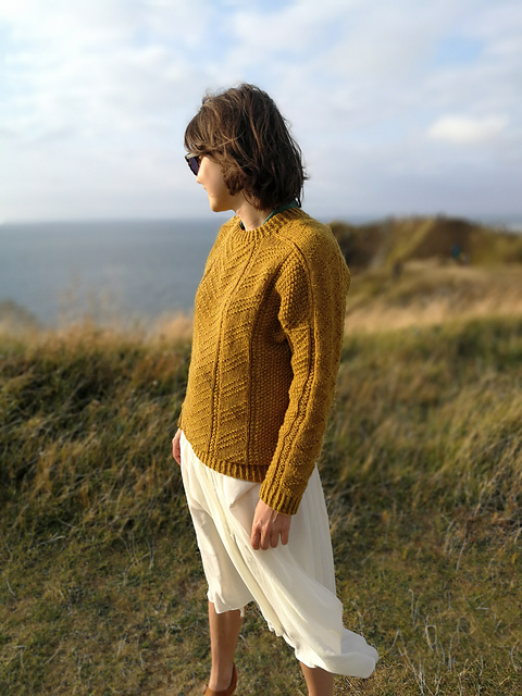 A woman stand on grass looking out to sea wearing a textured, hand knit sweater. Mr Rochester sweater knitting pattern by Alice Hammer knitted using The Fibre Co. Lore