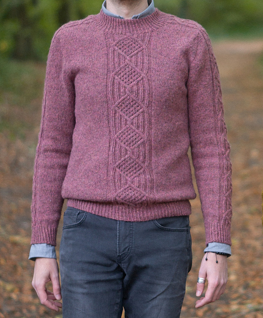 Cosy up of a man wearing a cabled sweater in the woods. Mens cables sweater pattern. Wuthering Heights by Les Tricoteurs Volants knitted using The Fibre Co. Lore