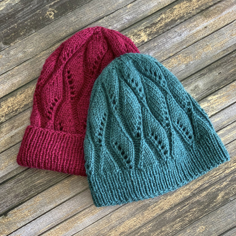 Two versions of the Lydia hat. They both have a diamond shape lace pattern, but one has a folded brim and one doesn't.