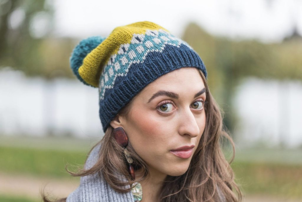A woman looks at the camera wearing a hand knit colour work hat. Rooda Hat Knitting Pattern by Simone Bechtold using The Fibre Co. Cumbria