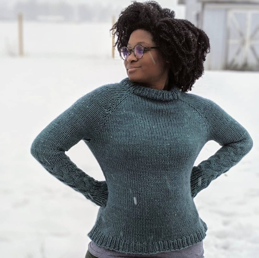 Woman stands in the snow wearing a cosy hand knit pullover | Beau Pulli by Safiyyah Talley in The Fibre Co. Tundra