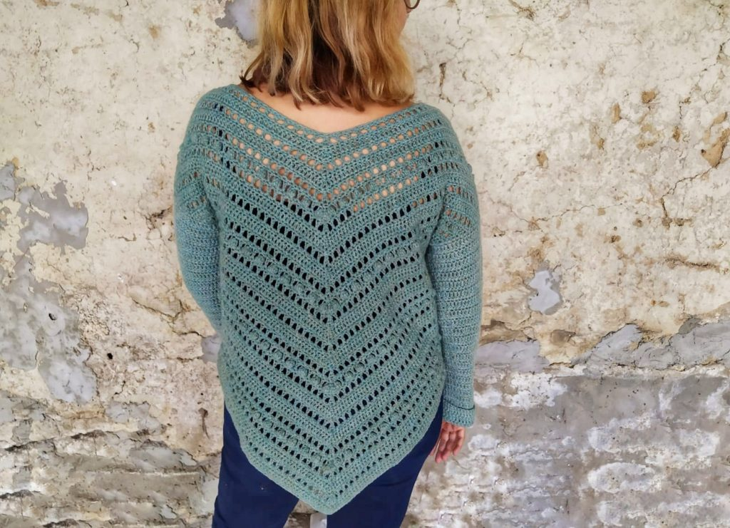 Woman stands in front of a distressed wall with her back to the camera wearing a crochet pullover with a decorative back panel. | Crochet pullover pattern. Anduril Pullover by Nomad Stitches in The Fibre Co. Lore