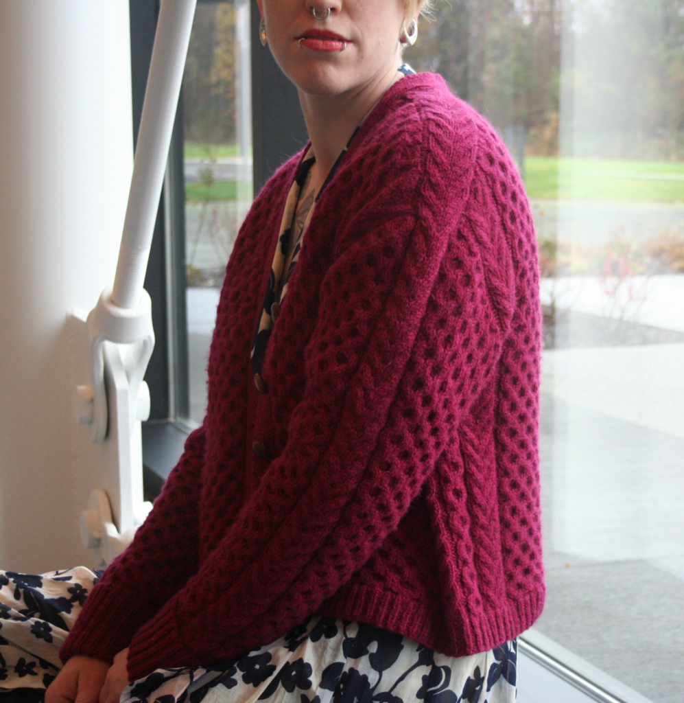 Woman sits in front of floor to ceiling windows and is photographed from the side wearing a hand knit honey comb cabled cardigan | Farrand by Allison Jane - Honey comb textured cardigan pattern knitting using The Fibre Co. Cumbria