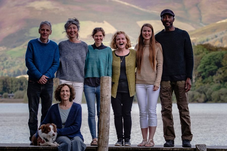 The Fibre Co. team stand on some decking over a lake. They are all wearing knitted garments and smiling at the camera. Our founder Daphne is at the front, sat with her legs over the water, and her dog Arlo beside her.