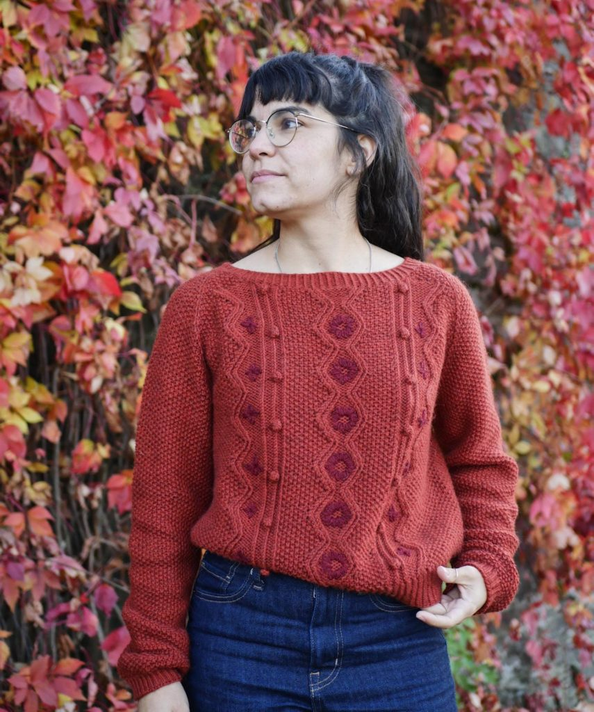Woman standing in front of a wall covered in autumn foliage poses in a decorative hand knit sweater. She looks away from the camera with one hand on her hip. | Dame Sweater by Marion Em knitted using The Fibre Co. Cumbria
