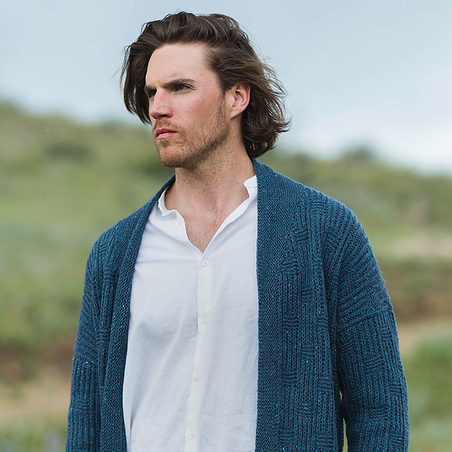 Man standing in a field wearing a dark blue cardigan that is loose fitting and open. | Straightaway Cardigan by Mone Dräger