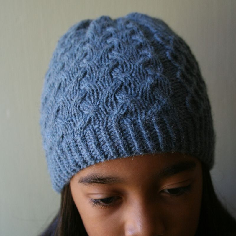 Heavily cabled, pale blue hat with a twisted rib brim.