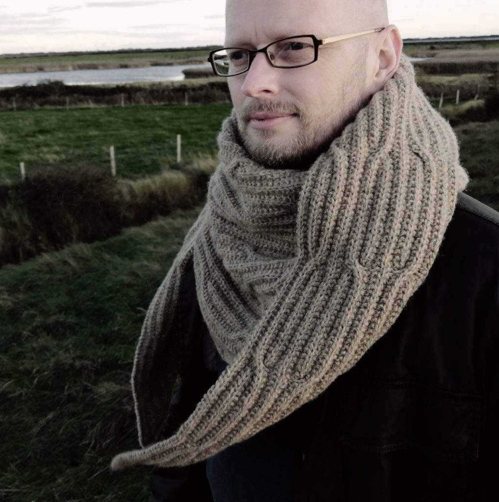 Man wearing a large hand knit wrap featuring a cable and rib design. | Tide Turner by Russell Sansom in The Fibre Co. Lore