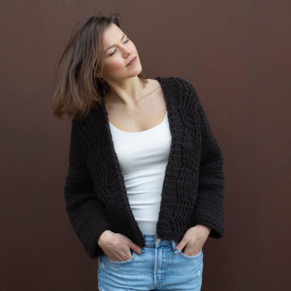 A woman is photographed flipping her hair with hands in her jeans pockets. She's wearing an open front crochet cardigan over a white t-shirt. | Secret Path Cardigan by Ana D in The Fibre Co. Tundra yarn.