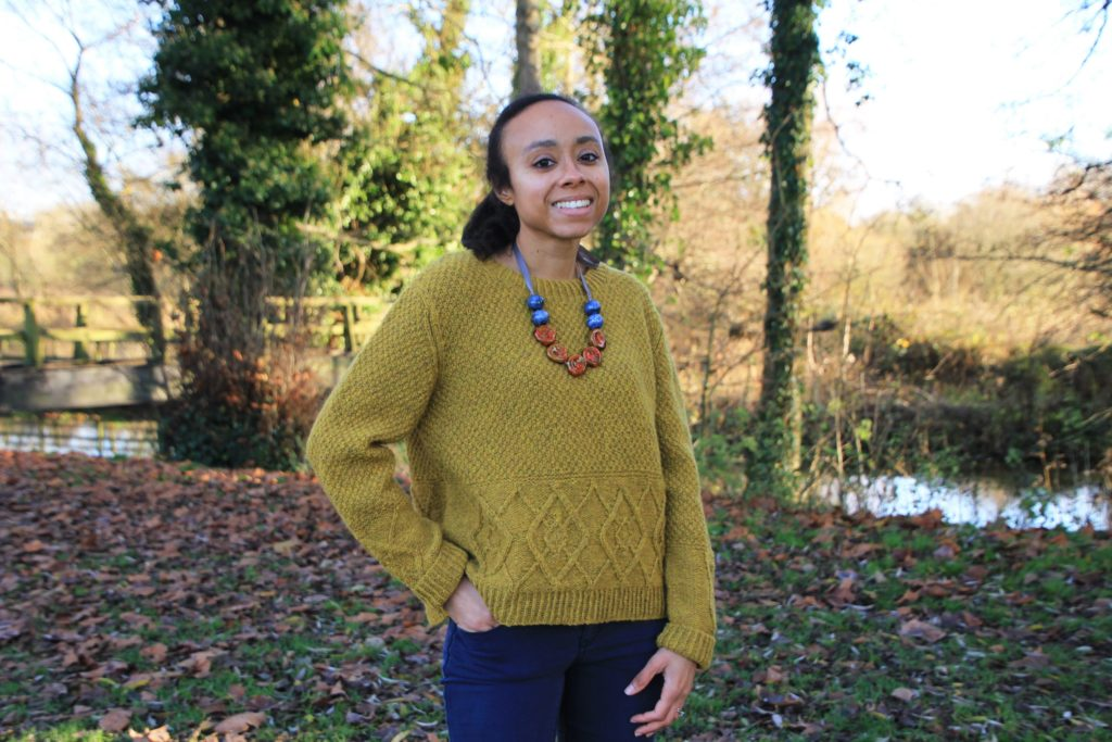Woman stands in woodland wearing a hand knit sweater with cable motif. She is smiling at the camera with one hand in her jeans pocket | Caledonia sweater knitting pattern by Sylvia Watts-Cherry knitted using The Fibre Co. Lore