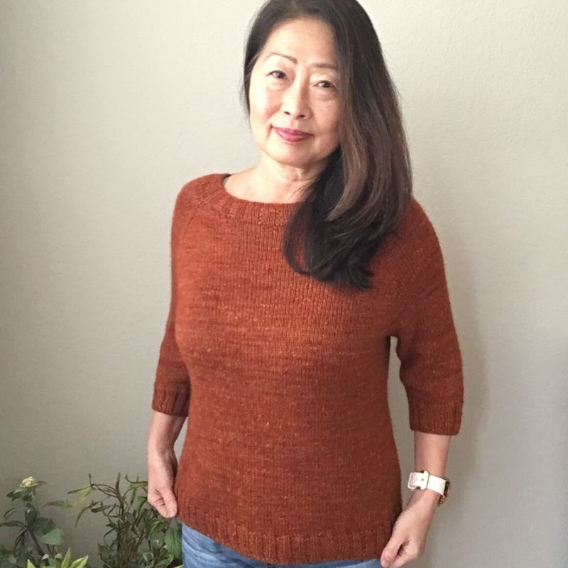 Camay wears a burnt orange hand-dyed raglan sweater