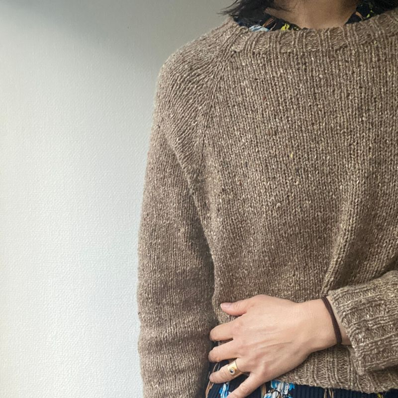 Elaine is wearing a beige tweed raglan sweater