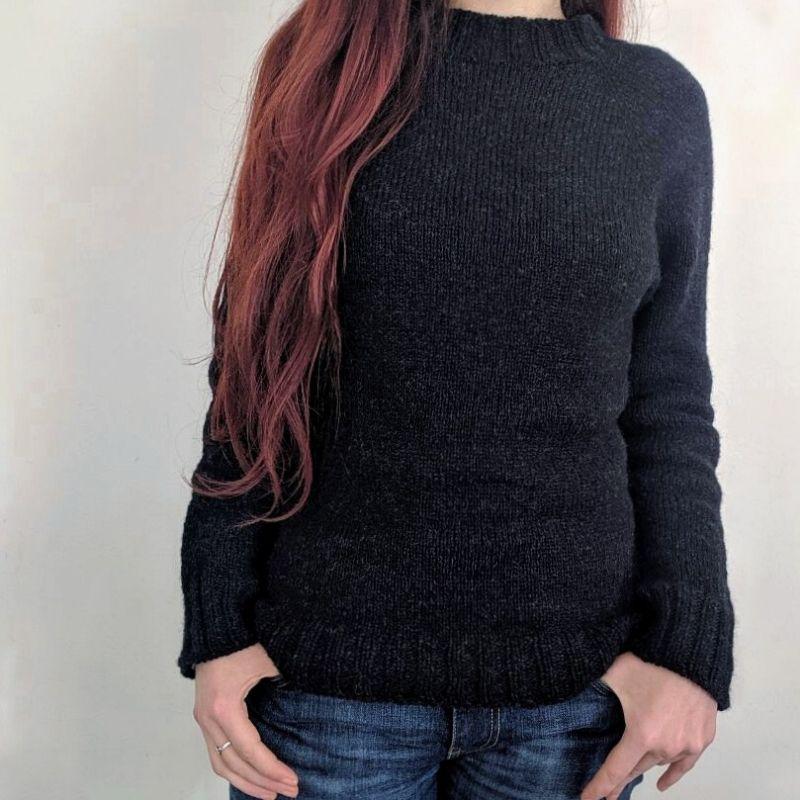Fran wears a black heathered raglan sweater