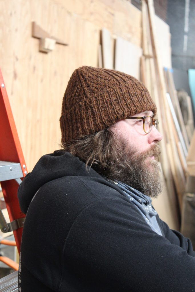 A carpenter wears a hand knit hat with rolled brim. He has a long beard and wears a black hoody in his studio. Hendren Hat Knitting Pattern by Julie Robinson