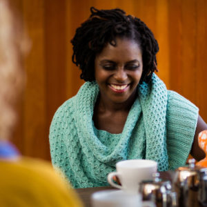 A woman sits laughing in a cafe wearing an aqua green shawl with a honey comb texture | Glykos Shawl Knitting Pattern