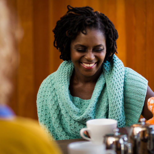 A woman sits laughing in a cafe wearing an aqua green shawl with a honey comb texture   Glykos Shawl Knitting Pattern