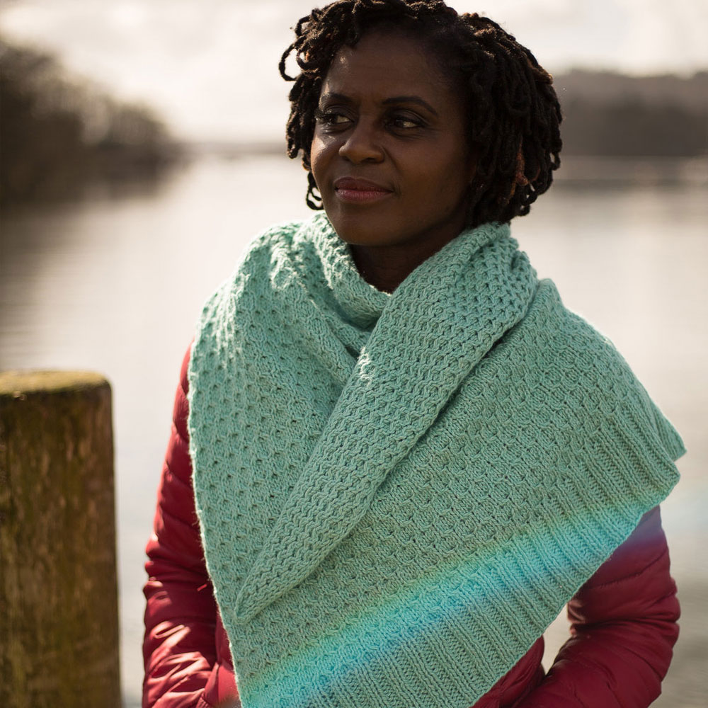 A woman stands by a lake in a red padded jacket with a big honey comb textured shawl wrapped around her | Glykos Shawl Knitting Pattern in The Fibre Co. Luma