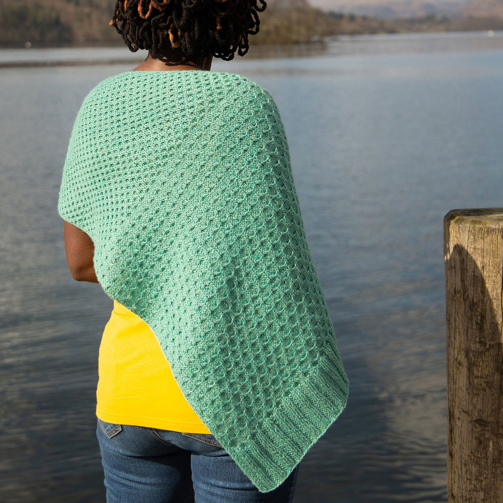 A woman stands looking out over a lake wearing an aqua green shawl with a honey comb texture | Glykos Shawl Knitting Pattern