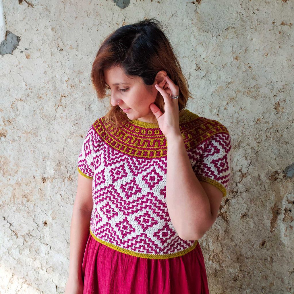 Teotihuacan Top by Nomad Stitches in The Fibre Co. Cumbria Fingering | Woman standing in front of a distressed stone wall wearing a colourful crochet top with a mosaic design