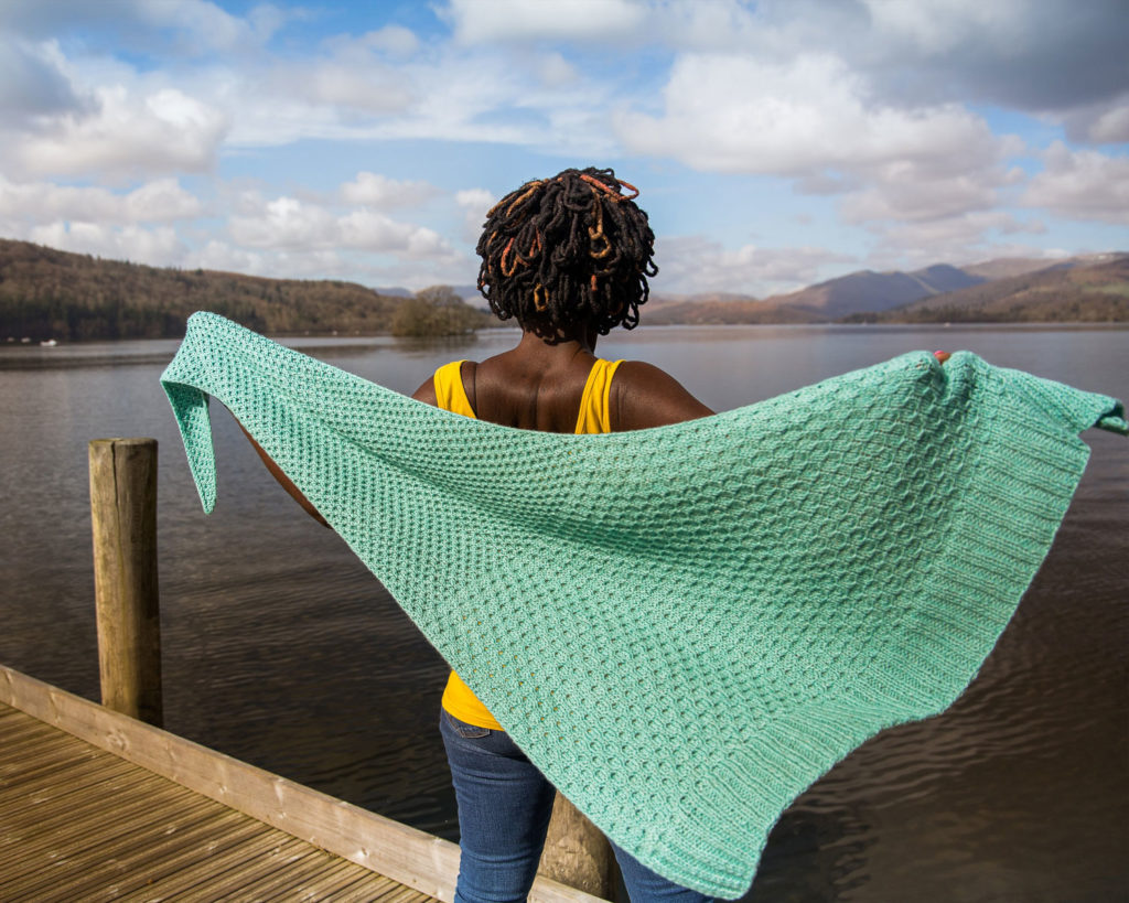 A woman stands looking out over a lake with her arms outstretched to show the aqua green shawl she is wearing | Glykos Shawl Knitting Pattern