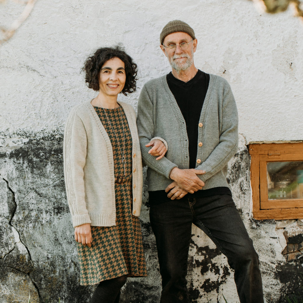 A couple smile at the camera, linking arms in front of a white stone wall. They wear v-neck cardigans that are hand knit for them | Lowther Cardigan Knitting Pattern