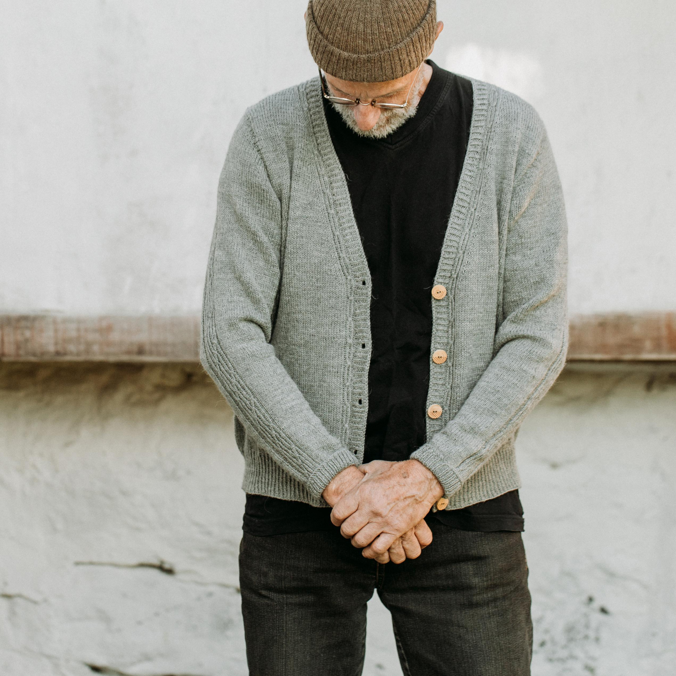 Ingemar is wearing a v-neck cardigan over a black t-shirt and jeans. He has his hands clasped in front of him and he's looking down. Lowther Cardigan Knitting Pattern