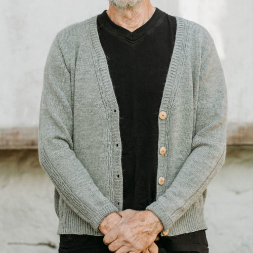Close up of a man wearing a grey, hand knitted, v-neck cardigan on black t-shirt and jeans   Lowther Fingering Cardigan Knitting Pattern