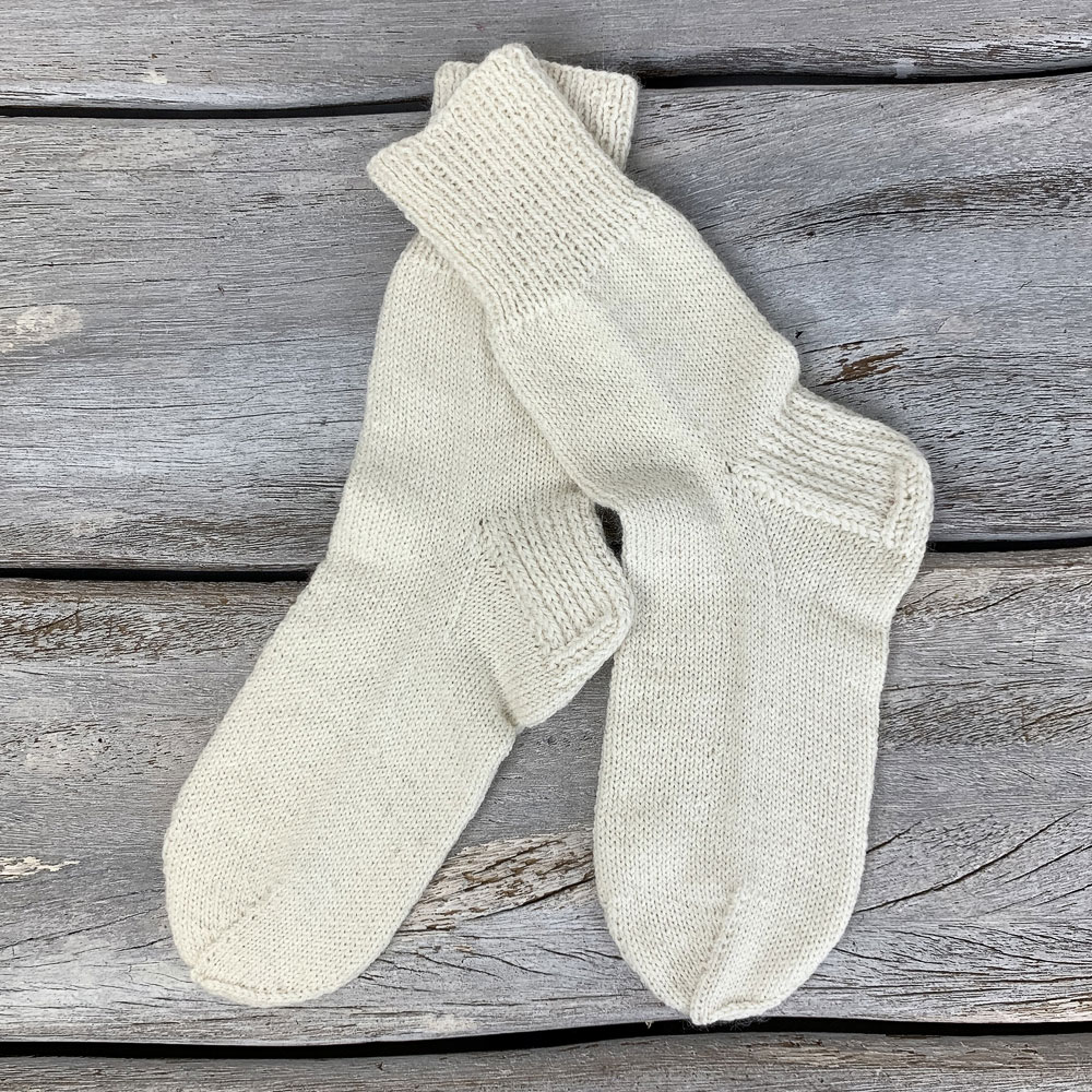 A pair of white hand knit socks | How to knit socks