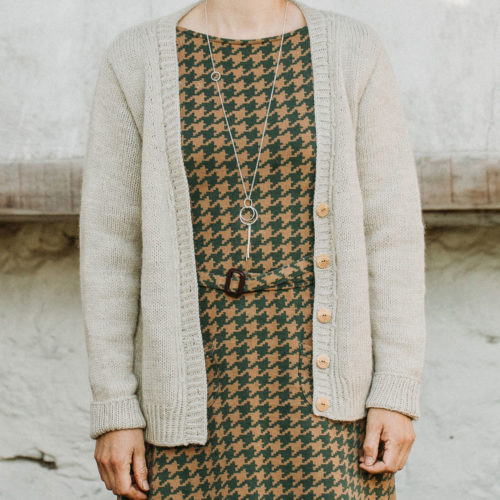 Close up photo of a woman wearing a light beige v-neck cardigan over a hounds tooth print dress with matching belt  Lowther Worsted Cardigan Knitting Pattern