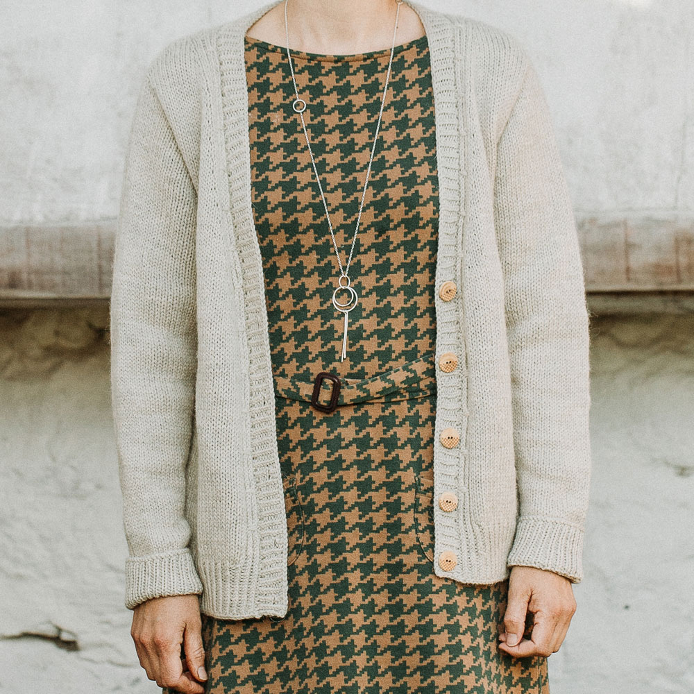 Close up photo of a woman wearing a light beige v-neck cardigan over a hounds tooth print dress with matching belt| Lowther Worsted Cardigan Knitting Pattern