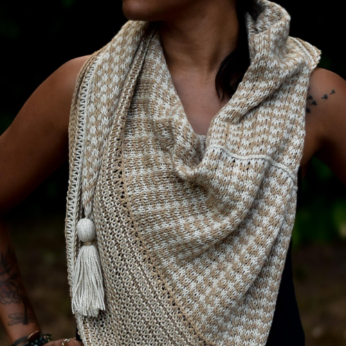 Woman wearing the Drift Blanket Shawl which is knitted in two colours of Luma - Blanca and Flax