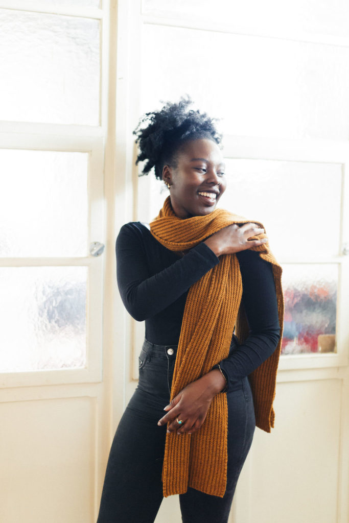 Woman standing in a light bright space with frosted windows behind her throws are very long scarf over her shoulder - Gifts you can make - Atmosphere scarf in The Fibre Co. Cumbria