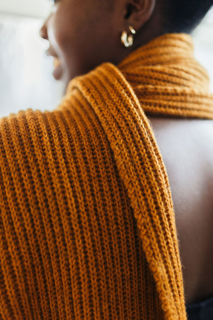 Close up from behind of an ribbed scarf around a woman's neck. Atmosphere is a classic gift you can make using The Fibre Co. yarn.