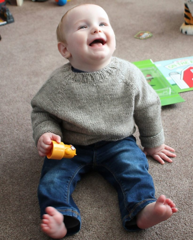 A baby wearing a wool sweater and jeans sits on the floor with a plastic toy in hand looking up and laughing. | One Sweater
