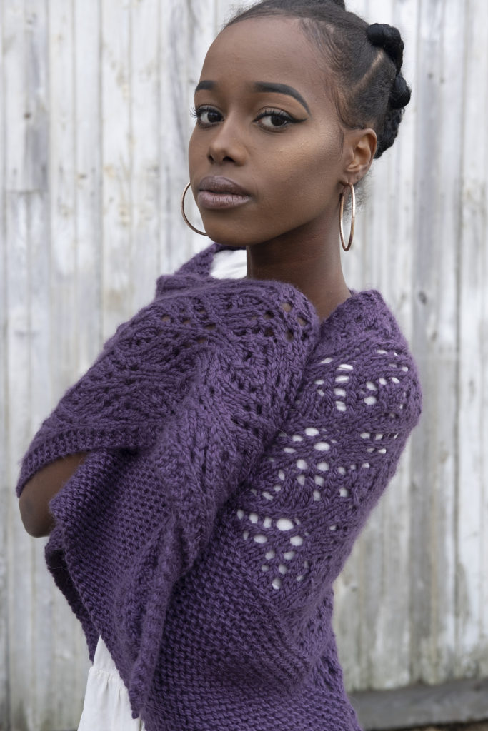 A woman stands in front of a faded wood fence looking straight at the camer. She is wearing a lace shawl knit from bulky yarn. | This is a quick gift you can knit