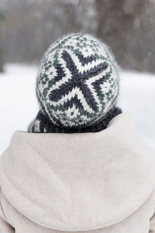 The crown of a colour work hat worn in the snow