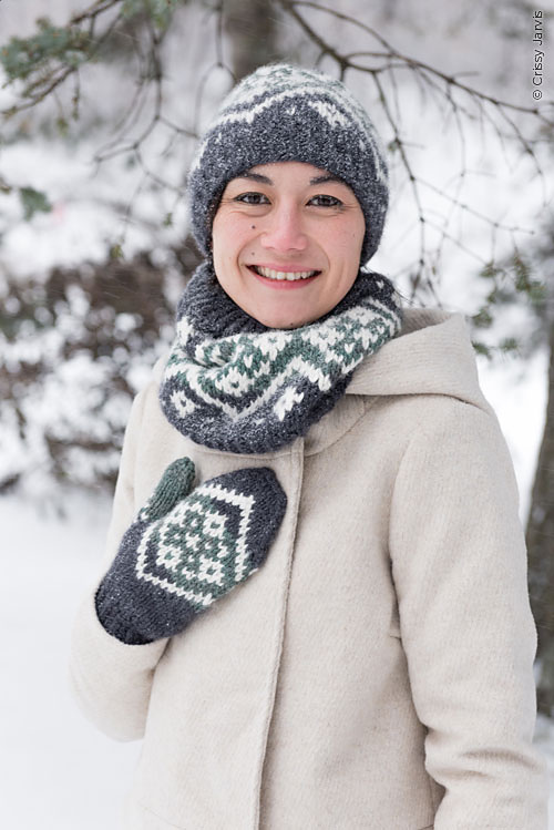 Quick gifts you can knit - Hat, cowl and mitten set. The woman is wearing the colour work accessories in the snow and she is smiling at the camera