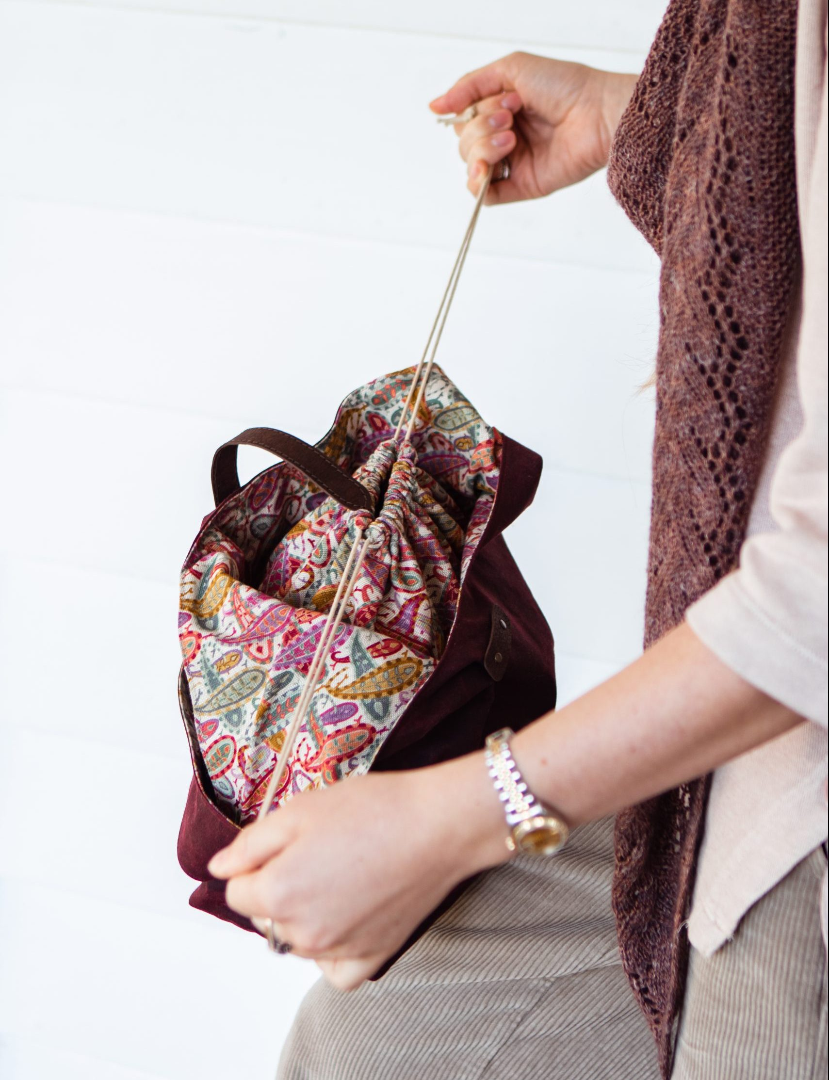 A woman is pulling the drawstring inside her bag closed. The lining is bursting with colour and a paisley pattern