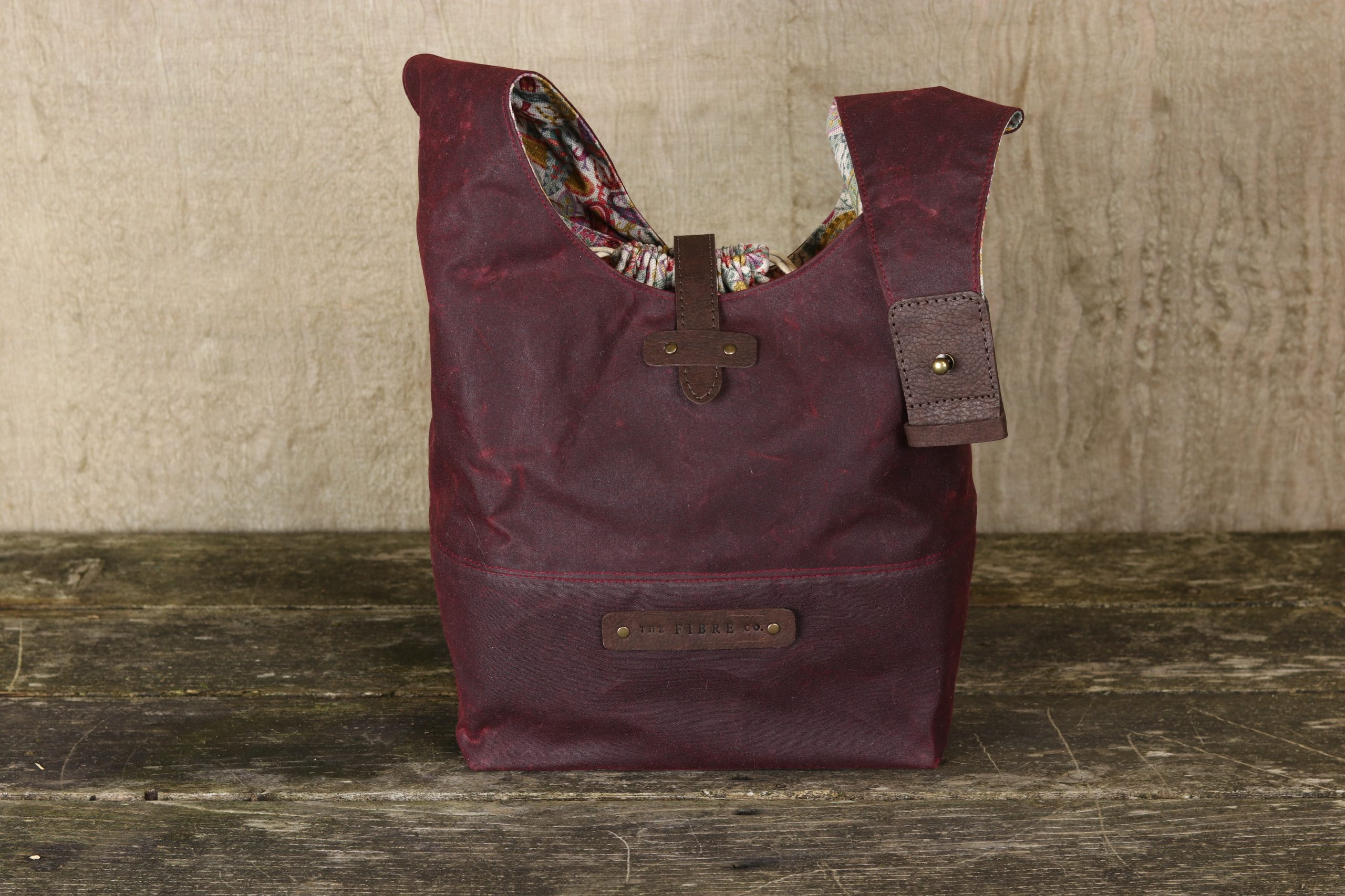Waxed cotton bag with vegan leather details and brass handware. The image shows that you can release the bag strap.