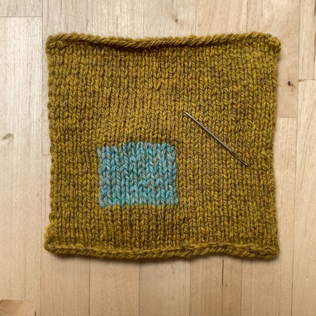 A mustard coloured square of hand knit fabric on a desk top with with a patch of Swiss darned visible mending in teal.