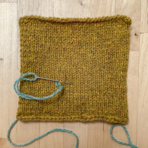 A mustard coloured square of hand knit fabric on a desk top with a single stitch of light teal blue in the fabric. A darning needle is making the second stitch.