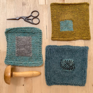 3 squares of handknit fabric lie on a desk, along with a pair of scissors, a darning mushroom and a needle