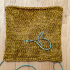 A mustard coloured square of hand knit fabric on a desk top with a single stitch of light teal blue in the fabric. A darning needle is making the second leg of the second stitch.