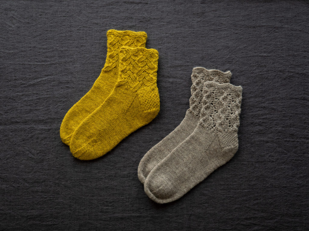 Two pairs of lace socks on a dark background. The left pair is yellow and the right pair is grey.| Mind Garden Socks in The Fibre Co. Amble