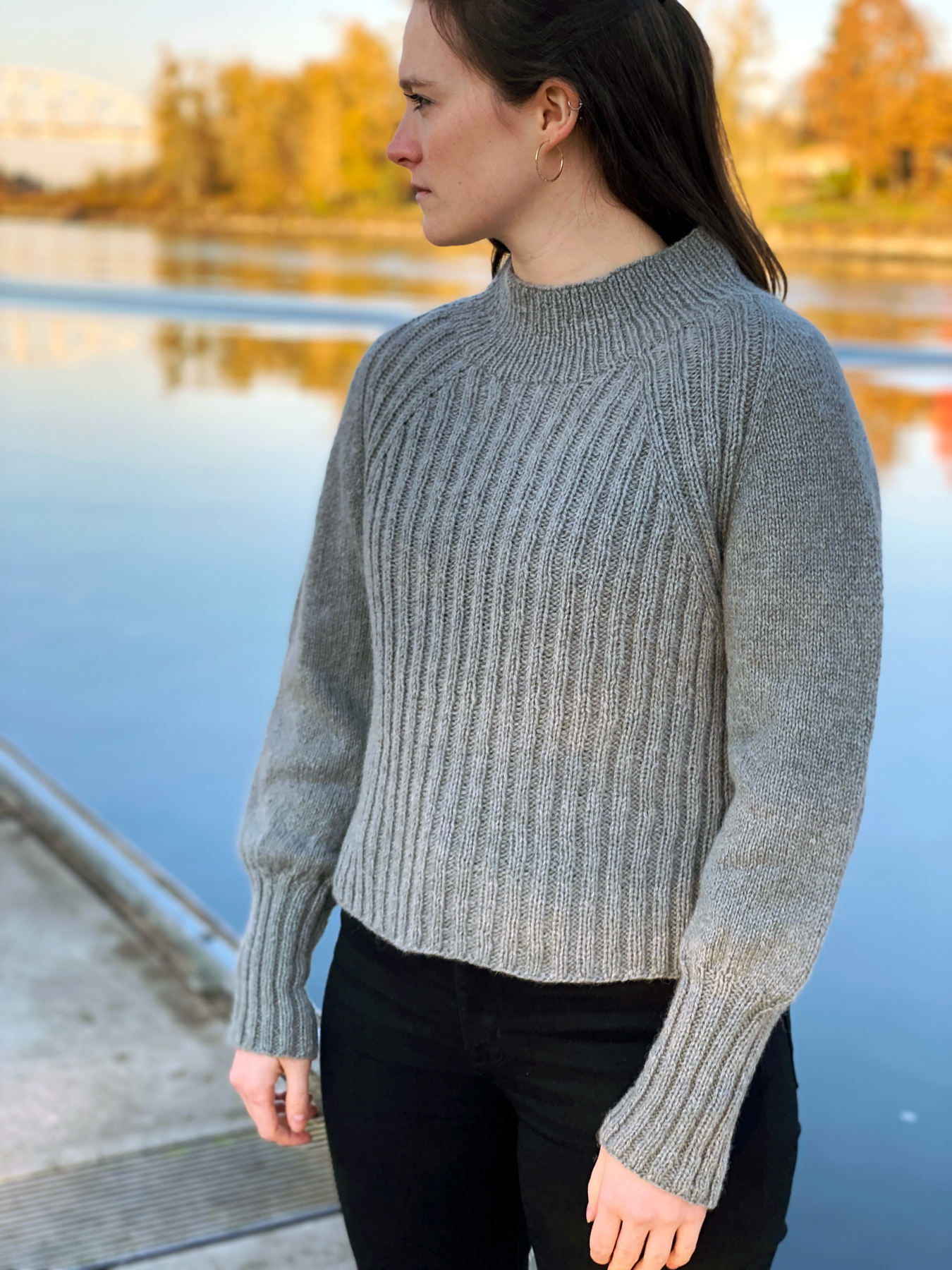 A woman wearing a wide rib sweater is standing on the edge of a still lake.   Santiam Canyon pullover knitted using The Fibre Co. Lore